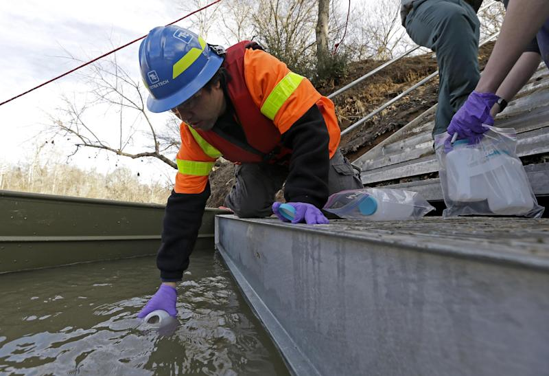 Didi Fung, a contractor for the Environmental Protection Agency, collects water samples from the Dan River as state and federal environmental officials continued their investigations of a spill of coal ash into the Dan River in Eden, N.C., Wednesday, Feb. 5, 2014. Duke Energy estimates that up to 82,000 tons of ash has been released from a break in a 48-inch storm water pipe at the Dan River Power Plant on Sunday. (AP Photo/Gerry Broome)