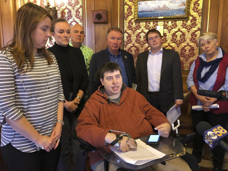 """Democratic state Rep. Jimmy Anderson, center, who is paralyzed and uses a wheelchair, says it is """"offensive,"""" """"disappointing"""" and """"frustrating"""" that Republicans did not consult with him before proposing ways to accommodate his needs, Tuesday, Oct. 8, 2019, in Madison, Wis. Republicans who control the Wisconsin Assembly intend to change their rules to allow a paralyzed Democratic lawmaker to phone into committee meetings he can't attend in person. Anderson, surrounded by Democratic colleagues, told reporters at the state Capitol that Republicans also should have spoken with a disability rights attorney before crafting the proposals. (AP Photo/Scott Bauer)"""