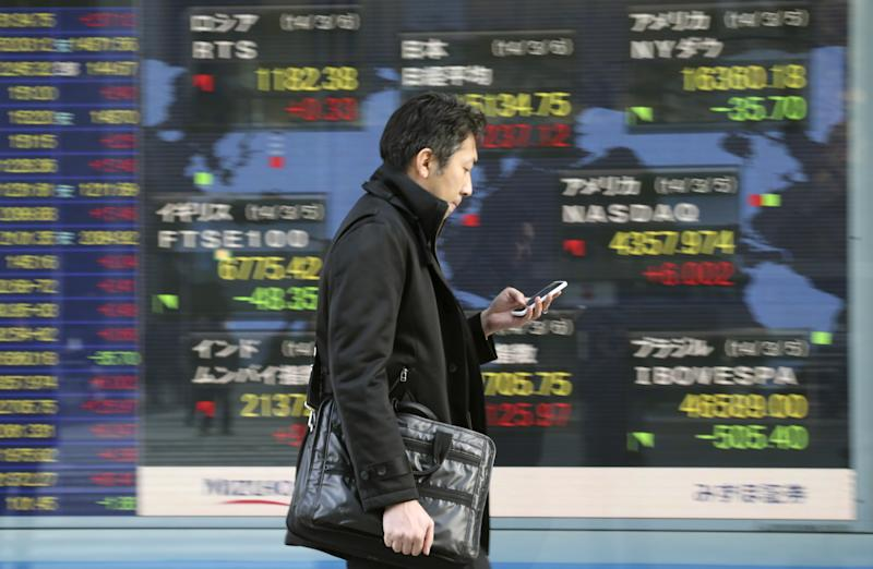 A man walks by an electronic stock board of a securities firm in Tokyo, Thursday, March 6, 2014. Shares were mostly higher in Asia on Thursday as the standoff over Ukraine between Russia and the West continued to ease and the yen weakened. (AP Photo/Koji Sasahara)