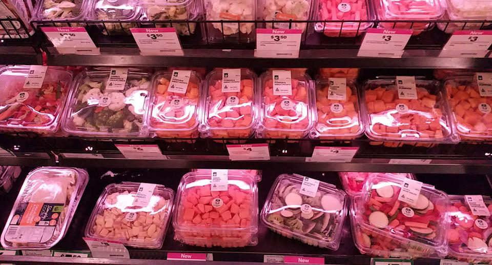 A Woolworths supermarket shelf with pumpkin, broccoli, cauliflower and other vegetables. They are in plastic containers.