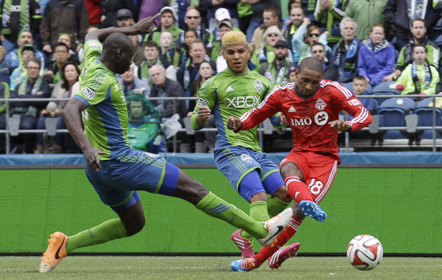 Toronto FC's Jermain Defoe, right, kicks a goal ahead of the defense of Seattle Sounders' Djimi Traore, left, and DeAndre Yedlin, center, in the first half of an MLS soccer match on Saturday, March 15, 2014, in Seattle. (AP Photo/Ted S. Warren)