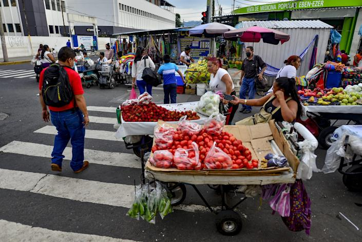 Vegetable sellers sit by the carts.