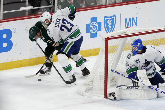 Vancouver Canucks' Alexander Edler (23), of Sweden, keeps Minnesota Wild's Zach Parise, left, in check as Canucks goalie Jacob Markstrom of Sweden, watches during the first period of an NHL hockey game Thursday, Feb. 6, 2020, in St. Paul, Minn. (AP Photo/Jim Mone)