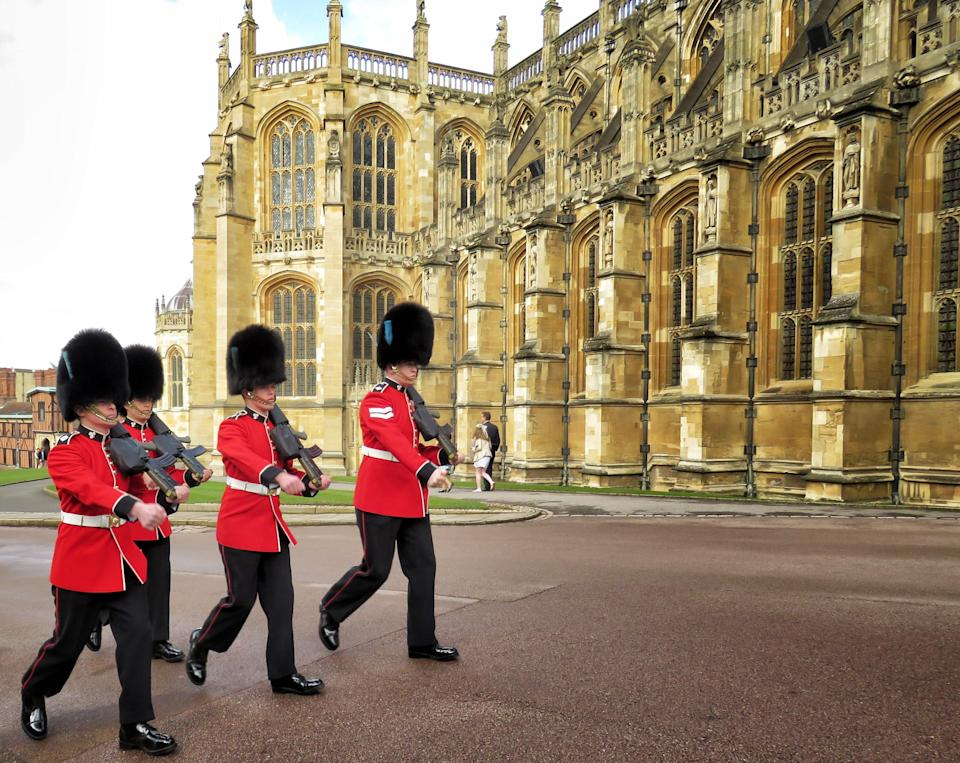 A beautiful picture of Buckingham Palace guards patrolling in their red and black uniform