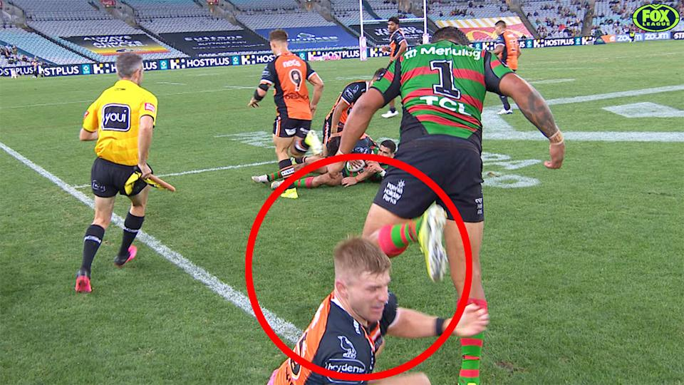 Pictured here, Latrell Mitchell kicks out towards Tigers forward Luke Garner.