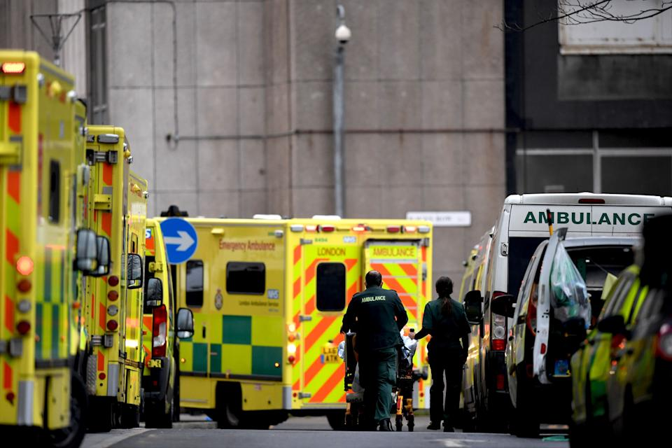 Paramedics wheel a patient on a trolley past a line of ambulances outside the Royal London hospital in London on January 12, 2021 as surging cases of the novel coronavirus are placing health services under increasing pressure. - People who flout coronavirus lockdown rules are putting lives at risk, the British government said on Tuesday, as cases surge to record highs and rumours swirl of potentially tougher restrictions. Britain is currently in its third lockdown, with schools and non-essential shops closed, as a new strain of the virus spreads rapidly across the country. (Photo by DANIEL LEAL-OLIVAS / AFP) (Photo by DANIEL LEAL-OLIVAS/AFP via Getty Images)