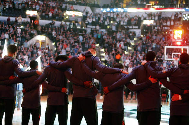 <p>Members of the Phoenix Suns stand arm-in-arm during a moment of silence for the victims of a deadly church shooting in Texas before an NBA basketball team against the San Antonio Spurs, Sunday, Nov. 5, 2017 in San Antonio. (Photo: Ronald Cortes/AP) </p>