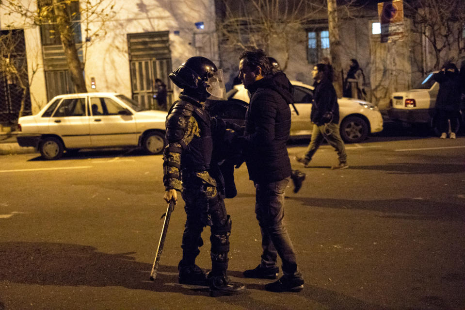 In this photograph taken Saturday, Jan. 11, 2020, a protester confronts an Iranian police officer while demonstrators gather in front of Amir Kabir University in Tehran, Iran, to remember victims of a Ukrainian airplane shot down by an Iranian missile. On Monday, Jan. 13, 2020, online videos purported to show that Iranian security forces fired both live ammunition and tear gas to disperse demonstrators protesting against the Islamic Republic's initial denial that it shot down a Ukrainian jetliner. (AP Photo)