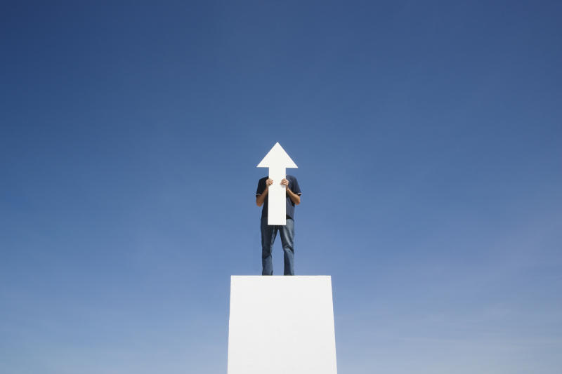 A man standing on a platform holding an arrow cut out pointing up