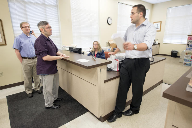 David Ermold (left) and his husband, David Moore (center), were among the couples who were denied marriage licenses by Kim Davis in 2015. (Lexington Herald-Leader via Getty Images)