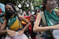 A boy, center, looks as women play drums during a march for Global Day of Action for access to legal, safe and free abortion, at a square in Caracas, Venezuela, Tuesday, Sept. 28, 2021. (AP Photo/Ariana Cubillos)