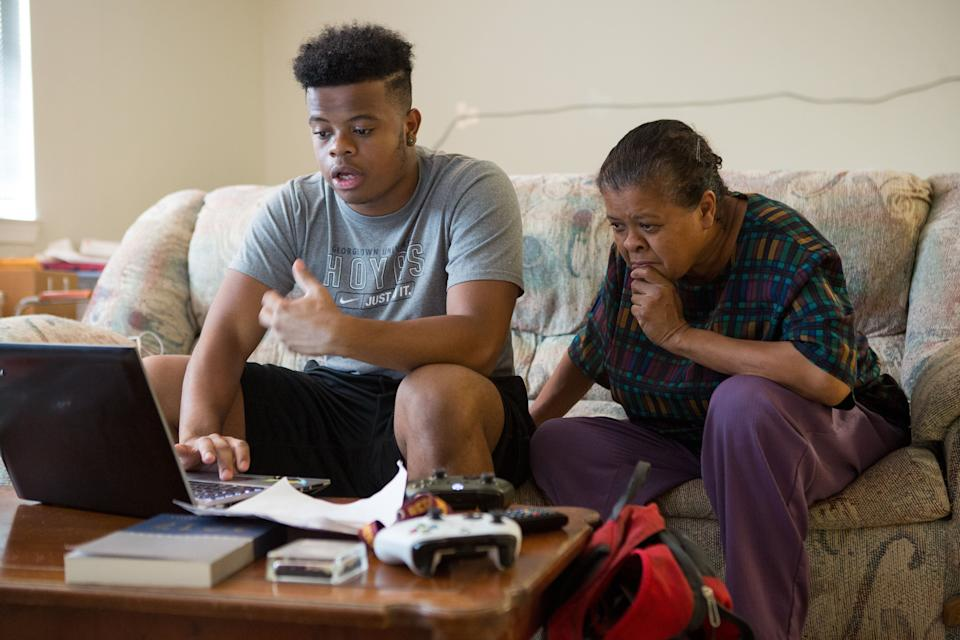 WASHINGTON, DC - JULY 23: Johnathon Carrington, 21, works on a cover letter for a job application as his mother Valerie Carrington looks on, at the family's apartment in the Tyler House, in the Sursum Corda neighborhood of Washington D.C., July 23, 2017. Johnathon, who graduated from Georgetown University this past spring, was the valedictorian of D.C.'s Dunbar High School in 2013 and is now looking for a job that will launch him into his career. (Photo by Allison Shelley/For The Washington Post via Getty Images)