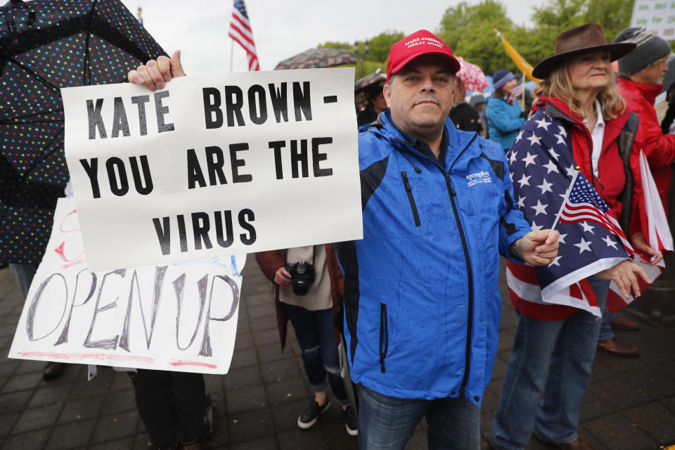 SALEM, OR - MAY 02: A man holds a sign saying Kate Brown you are the virus at the ReOpen Oregon Rally on May 2, 2020 in Salem, Oregon. Demonstrators gathered at the state capitol to demand a reopening of the state and to protest Gov. Kate Brown's stay-at-home order which was put in place to slow the spread of the coronavirus (COVID-19). (Photo by Terray Sylvester/Getty Images)