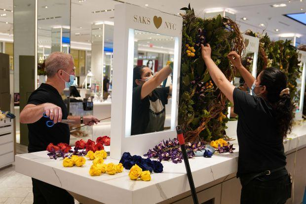 Worker put up flower display at Saks 5th Avenue in New York City.