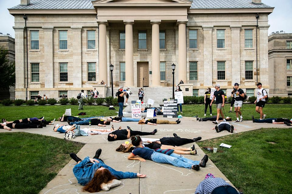 """Caleb Klipowicz, of the Campaign to Organize Graduate Students, speaks as people participate in a """"die-in"""" during a protest demanding more protections against COVID-19 on the University of Iowa campus, Thursday, Sept. 2, 2021, on the Pentacrest in Iowa City, Iowa."""