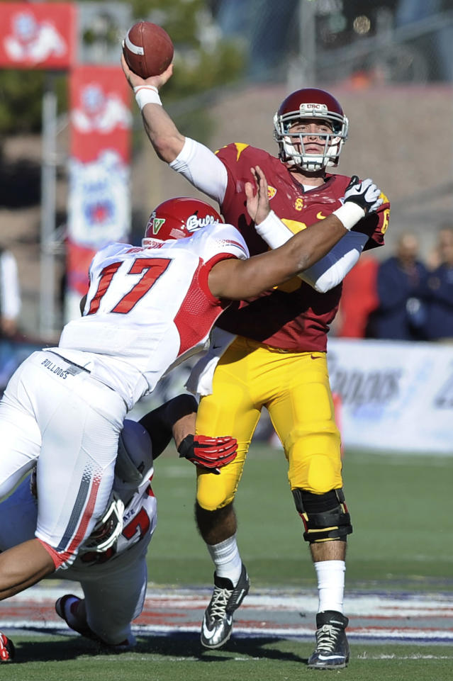 Southern California quarterback Cody Kessler (6) throws the ball as Fresno State linebacker Kyrie Wilson (17) closes in during the first quarter of the Royal Purple Bowl NCAA college football game, Saturday, Dec. 21, 2013 in Las Vegas. (AP Photo/David Cleveland)