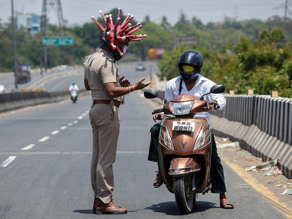 A police officer wearing a helmet depicting coronavirus requests a commuter to stay at home to limit the spreading of COVID-19, in Chennai, India, on March 28, 2020.