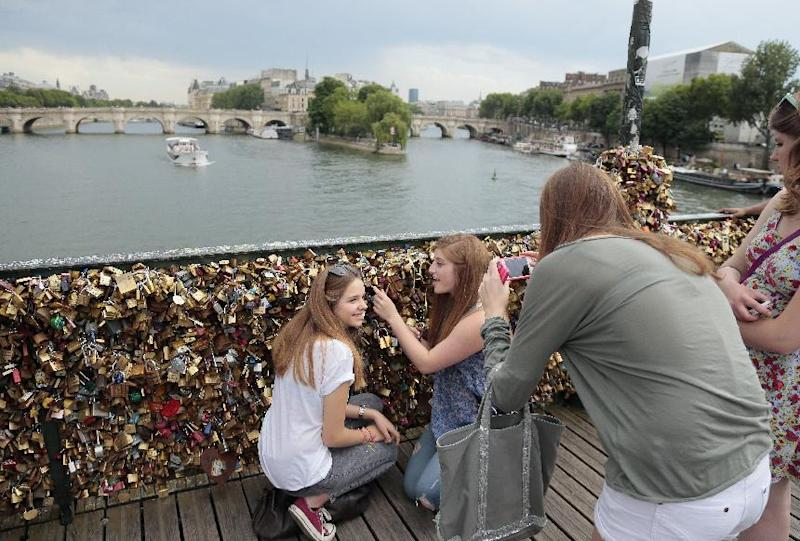 American tourists take photos by the so-called 'locks of love' on the Pont des Arts bridge over the Seine river in Paris on June 9, 2014