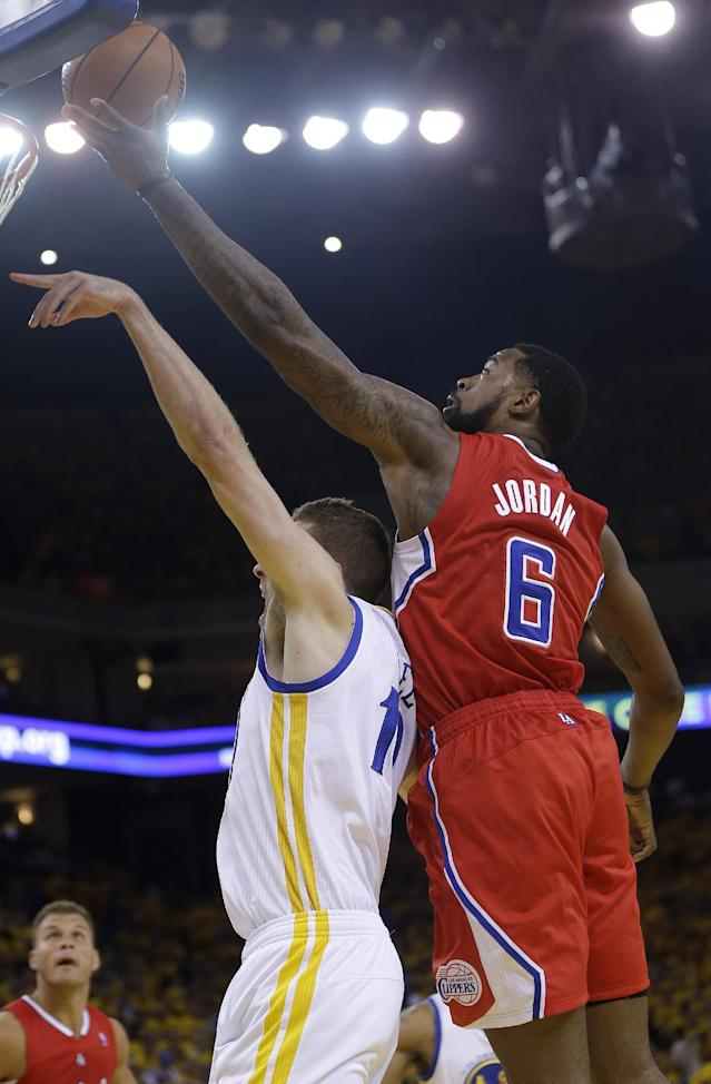 Los Angeles Clippers center DeAndre Jordan (6) reaches for the ball over Golden State Warriors power forward David Lee during the first quarter of Game 6 of an opening-round NBA basketball playoff series in Oakland, Calif., Thursday, May 1, 2014. (AP Photo/Marcio Jose Sanchez)