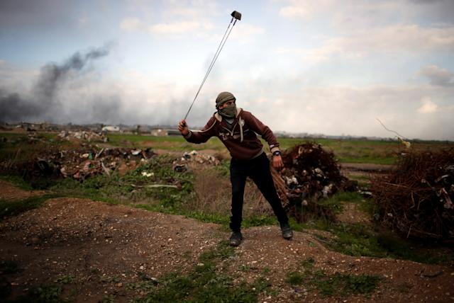 """<p>A Palestinian protester holds a sling as he poses for a photograph at the scene of clashes with Israeli troops near the border with Israel, east of Gaza City, Jan. 19, 2018. """"What I can do to stop Trump's decision on Jerusalem is to use this sling to hurl stones at Israeli soldiers with heavy weapons,"""" he said. """"My dream is to see all Arabs and Muslims united in one battle to restore our holy land."""" (Photo: Mohammed Salem/Reuters) </p>"""