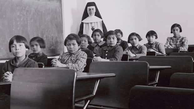 A group of female students and a nun pose in a classroom at Cross Lake Indian Residential School in Cross Lake, Man., in a February 1940 archive photo. The Piikani First Nation in southern Alberta will soon start looking for former residential school sites. (Library and Archives Canada - image credit)
