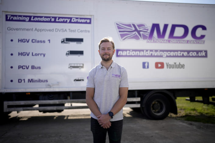 Laurence Bolton, the Managing Director of the National Driving Centre, poses for a portrait backdropped by a sign on the side of a truck showing different truck and vehicle categories, at the National Driving Centre in Croydon, south London, Wednesday, Sept. 22, 2021. Britain doesn't have enough truck drivers. The shortage is contributing to scarcity of everything from McDonald's milkshakes to supermarket produce. (AP Photo/Matt Dunham)