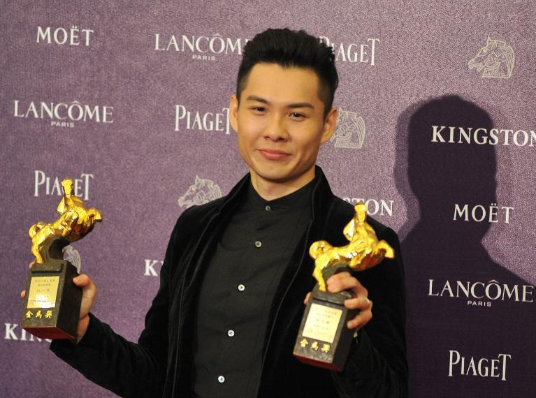 "Singapore film director Anthony Chen holds his trophies after winning the Best New Director and the Best Original Screenplay for ""Ilo Ilo"" at the 50th Golden Horse Film Awards in Taipei on November 23, 2013"