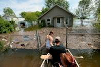 <p>Marissa Whitman, 20, wades in about three feet of floodwater from the swelling Mississippi River, while guiding a boat carrying her boyfriend Brendan Cameron and his mother, Tory Cameron, to their home along Pet Street, Sunday, May 5, 2019, in East Foley, Mo.</p>