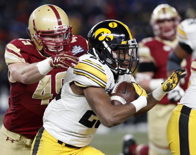 "Boston College linebacker Kevin Bletzer (49) prepares to tackle Iowa running back <a class=""link rapid-noclick-resp"" href=""/ncaaf/players/227377/"" data-ylk=""slk:Akrum Wadley"">Akrum Wadley</a> (25) who runs with the ball during the first quarter of the Pinstripe Bowl NCAA college football game, Wednesday, Dec. 27, 2017, in New York. (AP Photo/Kathy Willens)"