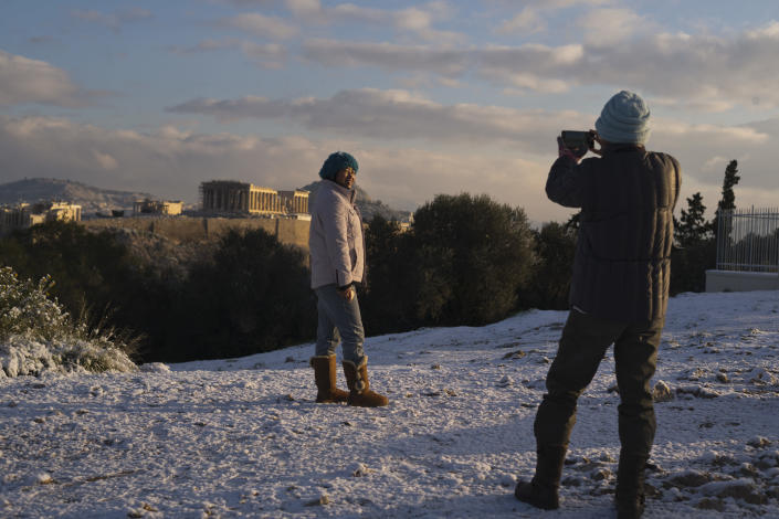 A tourist poses for a picture at Filopappos hill as at the background is seen the ancient Acropolis hill with the 500BC Parthenon temple, after snowfall in Athens, on Tuesday, Jan. 8, 2019. (AP Photo/Petros Giannakouris)