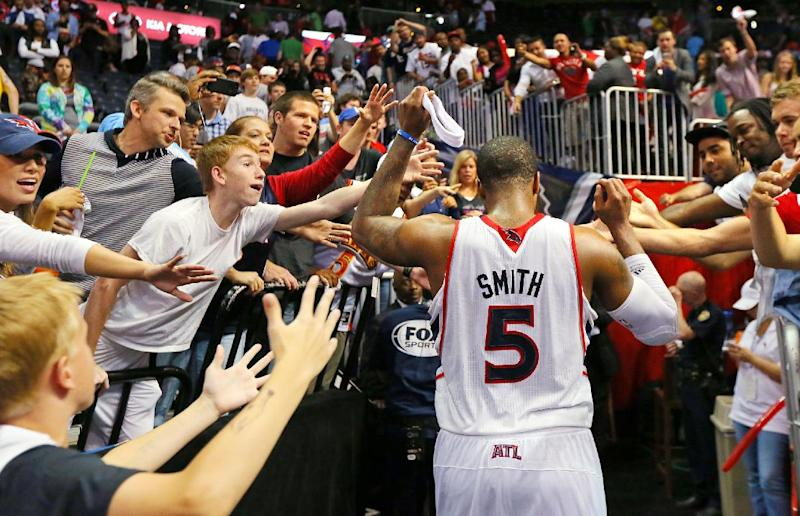 Atlanta Hawks fan give game hero Josh Smith high fives as he leaves the court after leading the Hawks to a 102-91 victory over the Pacers in Game 4 of their first-round NBA basketball playoff series game Monday, April 29, 2013, in Atlanta. The win ties the first round series 2-2.   (AP Photo/ Journal-Constitution, Curtis Compton)