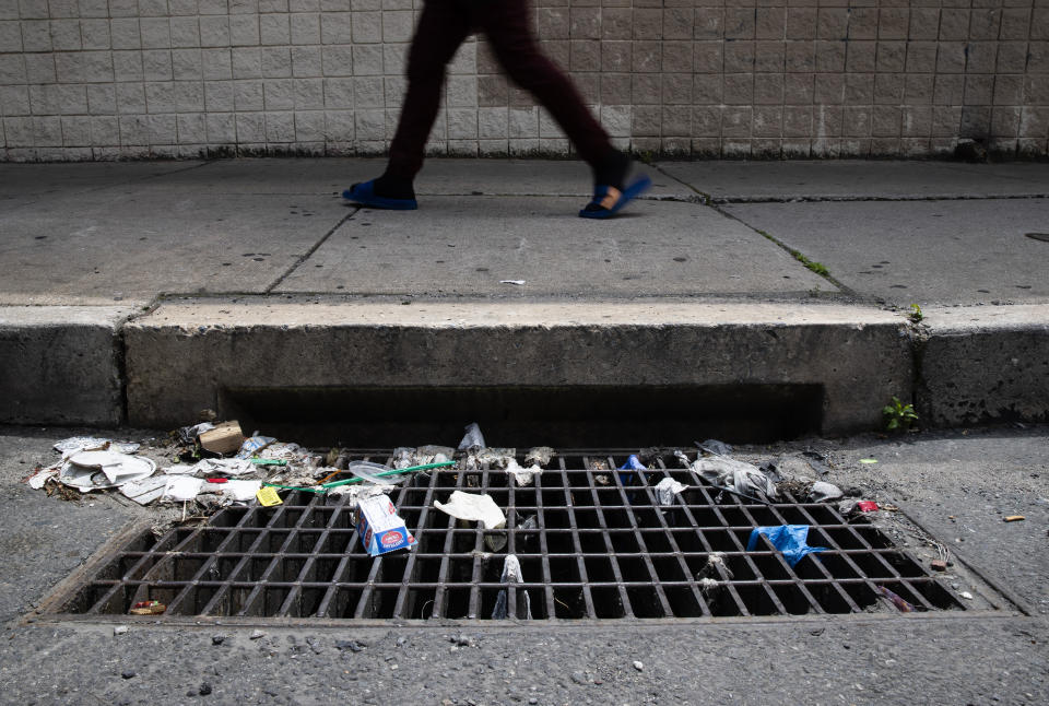 In this Monday, May 25, 2020 photo a person walks past a storm drain with discarded gloves and other trash in Philadelphia. Between mid-March, when the city's stay-at-home order was issued, and the end of April, most of the 19 sewer and storm water pumping stations in Philadelphia had experienced clogs from face masks, gloves and wipes residents had pitched into the potty, Philadelphia Mayor Jim Kenney said.(AP Photo/Matt Rourke)