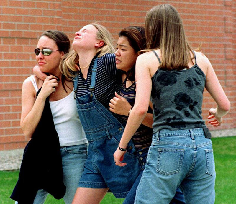 In this April 20, 1999, photo, young women head to a library near Columbine High School where students and faculty members were evacuated after two gunmen went on a shooting rampage in the school in the southwest Denver suburb of Littleton, Colo. (Kevin Higley/AP)
