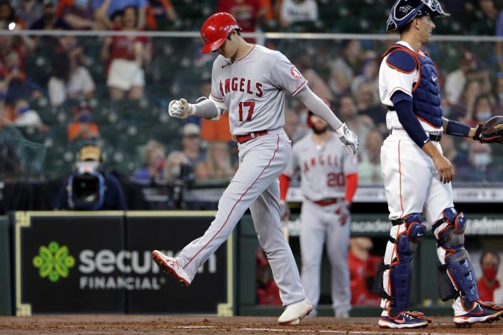 Los Angeles Angels designated hitter Shohei Ohtani (17) crosses the plate on his home run next to Houston Astros catcher Jason Castro, right, during the third inning of a baseball game Saturday, April 24, 2021, in Houston. (AP Photo/Michael Wyke)