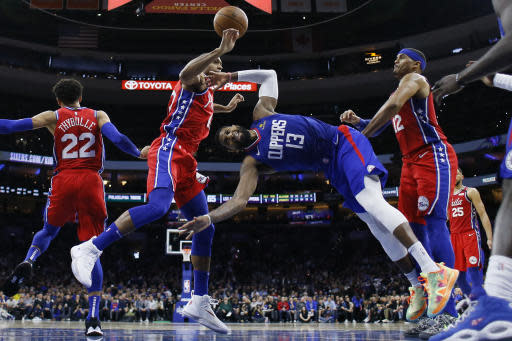 Los Angeles Clippers' Paul George (13) cannot get a shot past Philadelphia 76ers' Al Horford (42) Tobias Harris (12) and Matisse Thybulle (22) during the second half of an NBA basketball game, Tuesday, Feb. 11, 2020, in Philadelphia. (AP Photo/Matt Slocum)