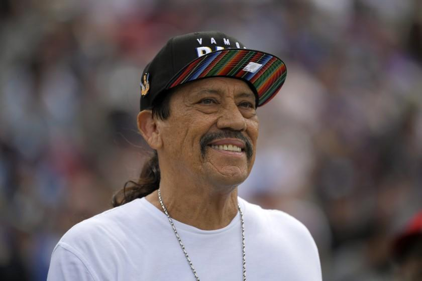 Danny Trejo smiling in a rainbow hat and white shirt