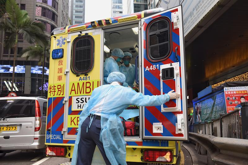 HONG KONG, CHINA - JANUARY 23: Health care members make first aid to people at an ambulance as they cover their faces with sanitary masks after the first cases of coronavirus have been confirmed in Hong Kong, China on January 23, 2020. On 22nd of January, China officially announced the Wuhan's virus outbreak can be transmitted human-to-human and implemented a public transportation and airport lockdown to slow down the spread of the virus. (Photo by Miguel Candela Poblacion/Anadolu Agency via Getty Images)