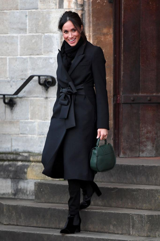 """<p>For the couple's first outing in Cardiff, the former actress chose an all-black look. In celebration of Wales, the 36-year-old donned jeans by Huit and teamed the look with a Stella McCartney <a href=""""https://www.harrods.com/en-gb/designers/stella-mccartney?redirectReason=product404"""" rel=""""nofollow noopener"""" target=""""_blank"""" data-ylk=""""slk:coat"""" class=""""link rapid-noclick-resp"""">coat</a> (£1,350), Tabitha Simmons <a href=""""https://www.farfetch.com/uk/shopping/women/tabitha-simmons-black-kiki-75-velvet-ankle-boots--item-12284152.aspx?clickref=1011l4EcinUu&utm_source=skimlinks_phg&utm_medium=affiliate&utm_campaign=PHUK&utm_term=UKNetwork&pid=performancehorizon_int&c=skimlinks_phg&clickid=1011l4EcinUu&af_siteid=305950&af_sub_siteid=1011l271&af_cost_model=CPA&af_channel=affiliate&is_retargeting=true"""" rel=""""nofollow noopener"""" target=""""_blank"""" data-ylk=""""slk:boots"""" class=""""link rapid-noclick-resp"""">boots</a> (£525) and an emerald DeMellier <a href=""""https://www.demellierlondon.com/the-mini-venice.html?color=146"""" rel=""""nofollow noopener"""" target=""""_blank"""" data-ylk=""""slk:handbag"""" class=""""link rapid-noclick-resp"""">handbag</a> (£295). <em>[Photo: Getty]</em> </p>"""