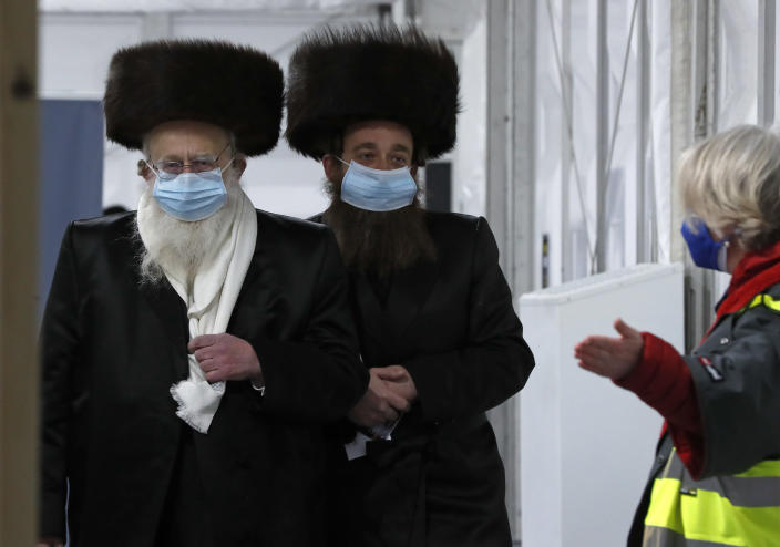 FILE - In this Saturday, Feb. 13, 2021 file photo, two men from the Haredi Orthodox Jewish community arrive at an event to encourage vaccine uptake in Britain's Haredi community at the John Scott Vaccination Centre in London. Thanks to an efficient vaccine roll out program and high uptake rates, Britain is finally saying goodbye to months of tough lockdown restrictions. From Monday May 17, 2021, all restaurants and bars can fully reopen, as can hotels, cinemas, theatres and museums, and for the first time since March 2020, Britons can hug friends and family and meet up inside other people's houses. (AP Photo/Frank Augstein, File)