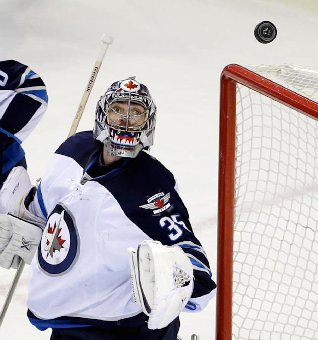 Winnipeg Jets goalie Al Montoya deflects a San Jose Sharks shot during the first period of an NHL hockey game Thursday, March 27, 2014, in San Jose, Calif. (AP Photo/Marcio Jose Sanchez)