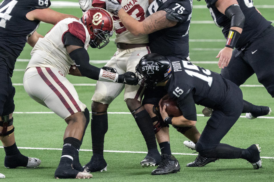 Oklahoma defensive lineman Perrion Winfrey grabs the face mask of Iowa State quarterback Brock Purdy (15) during the first half of the the Big 12 Conference championship NCAA college football game, Saturday, Dec. 19, 2020, in Arlington, Texas. (AP Photo/Jeffrey McWhorter)