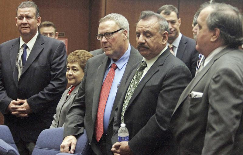 FILE - In this  Jan. 24, 2013 file photo, former Bell, Calif., city officials, from left,  Luis Artiga, Teresa Jacobo, George Cole, Oscar Hernandez and Victor Bello appear for a city corruption trial in a downtown Los Angeles courtroom. Los Angeles County prosecutors announced Tuesday, May 21, 2013, they intend to retry five former Bell city officials already convicted of misappropriating public funds by collecting exorbitant salaries.  Artiga was acquitted; the other four plus George Mirabal, not shown, were convicted in March, but jurors deadlocked on a handful of counts against each of them. (AP Photo/Los Angeles Times, Francine Orr, Pool, File)
