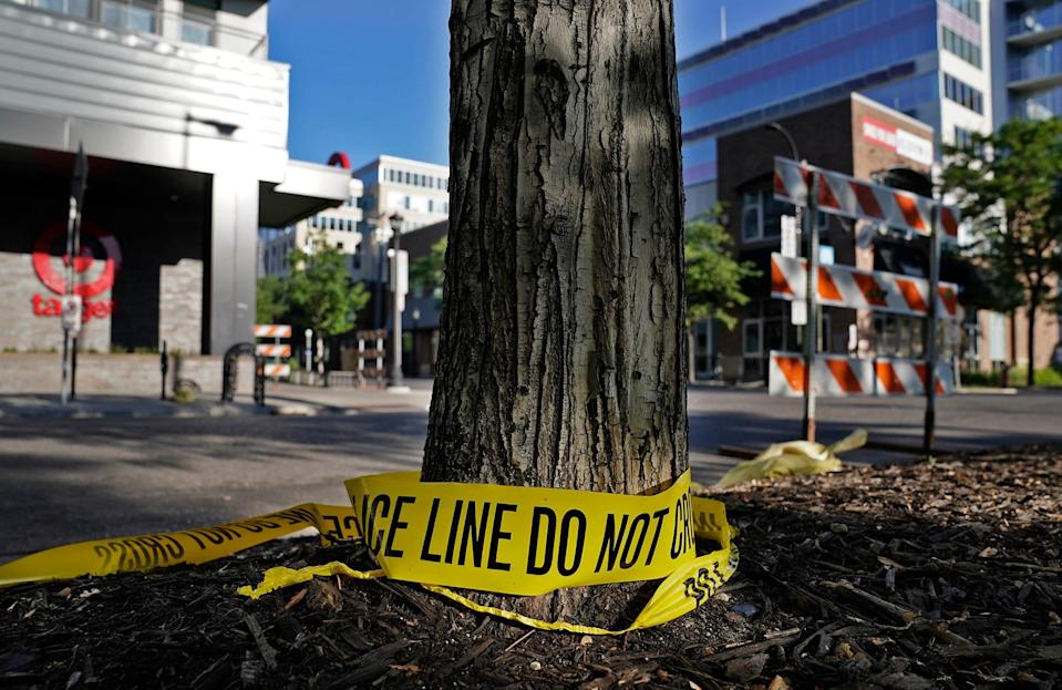 Discarded police tape lays outside a Target Monday, June 14, 2021, in Uptown Minneapolis.  Minneapolis police and witnesses say a woman was killed and multiple others were injured when an SUV struck a parked car and tossed it into demonstrators during a protest late Sunday in Minneapolis.