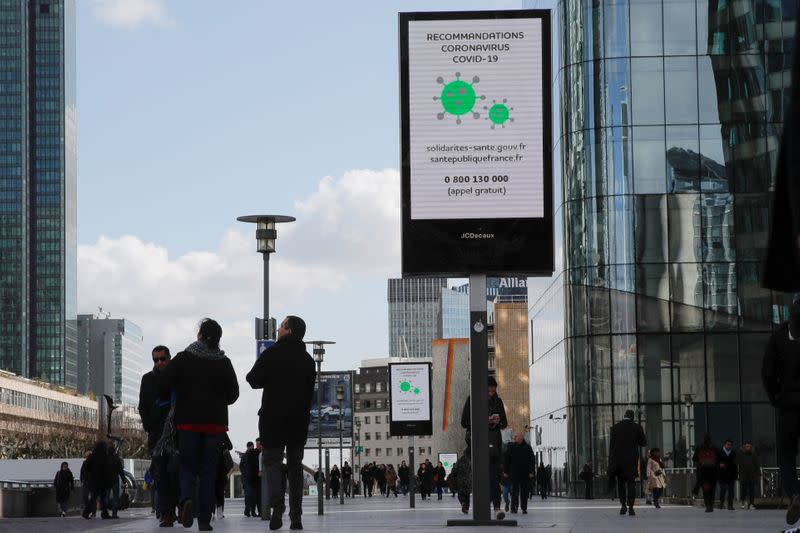 People walk pass a board with information about coronavirus at the financial and business district of La Defense