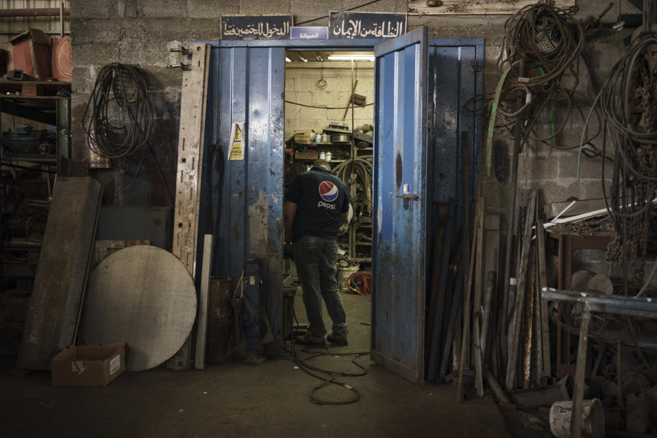 A Palestinian employee stands in a workshop at the Pepsi bottling plant in Gaza City, Monday, June 21, 2021. Israel on Monday eased some restrictions on the Gaza Strip however the Pepsi factory announced today that it was closing and laying off workers because raw materials needed to stay in business are still not coming. (AP Photo/Felipe Dana)