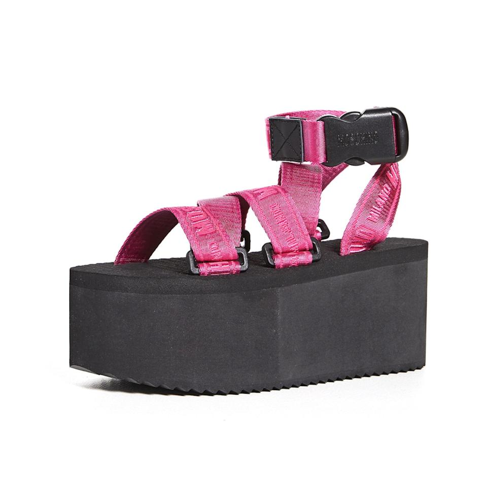 """If the thought of a shoe that's somewhere in the middle of sporty and avant garde intrigues you, you'll appreciate these Moschino platforms. They feature pink utility straps and an oversized sole that would look fabulous with dresses and <a href=""""https://www.glamour.com/gallery/jumpsuits-for-women?mbid=synd_yahoo_rss"""" rel=""""nofollow noopener"""" target=""""_blank"""" data-ylk=""""slk:jumpsuits"""" class=""""link rapid-noclick-resp"""">jumpsuits</a>. $190, Shopbop. <a href=""""https://www.shopbop.com/platform-sandal-moschino/vp/v=1/1541142393.htm?"""" rel=""""nofollow noopener"""" target=""""_blank"""" data-ylk=""""slk:Get it now!"""" class=""""link rapid-noclick-resp"""">Get it now!</a>"""