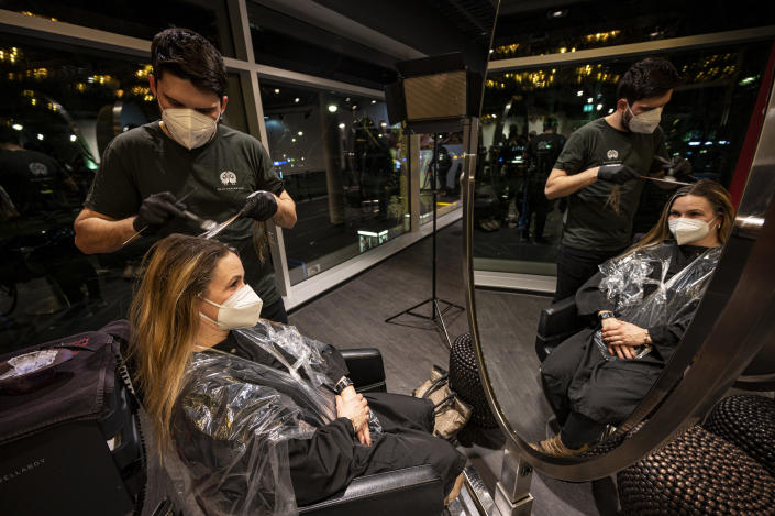 The first customer of Shan Rahimkhan's barbershop gets her hair cut and colored after the reopening in Berlin, Germany, early Monday, March 1, 2021. Hairdressers welcome customers in Germany after successfully lobbying the government to be allowed to reopen their doors while hospitality business and shops remain closed to battle the coronavirus pandemic. (Fabian Sommer/dpa via AP)