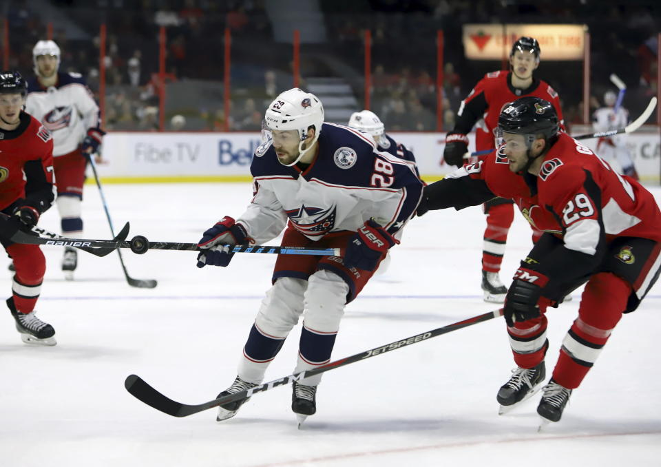 Columbus Blue Jackets right wing Oliver Bjorkstrand (28) uses his stick to juggle the puck at Ottawa Senators defenceman Cody Goloubef (29) looks on during the first period of an NHL hockey game in Ottawa, Saturday, Dec. 14, 2019. (Fred Chartrand/The Canadian Press via AP)