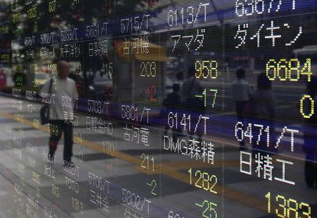 A pedestrian is reflected in an electronic board showing the various stock prices outside a brokerage in Tokyo August 13, 2014. Asian shares eked out modest gains on Wednesday, as investors remained cautious after downbeat data from China and Japan and as the crisis in Ukraine threatened a fragile economic recovery in Europe. REUTERS/Yuya Shino (JAPAN - Tags: BUSINESS)