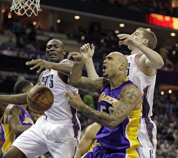 Los Angeles Lakers' Robert Sacre, center, loses the ball under the basket as the Charlotte Bobcats' Bismack Biyombo, left and Cody Zeller, right, battle during the first half of an NBA basketball game in Charlotte, N.C., Saturday, Dec. 14, 2013. (AP Photo/Bob Leverone)